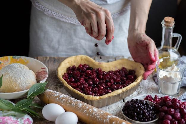 Повар наливает ягоды в тесто