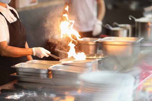 料理人は火で食べ物を準備します。フライパンで熱い炎。