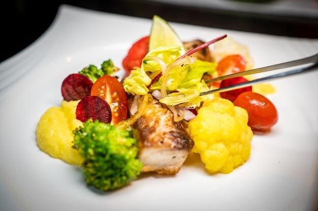 Готовим блюдо из рыбного филе с овощами при помощи щипцов. коста-рика гастрономия