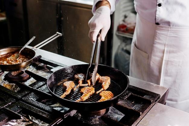 Повар готовит мясные ребра внутри черной металлической кастрюле на кухне