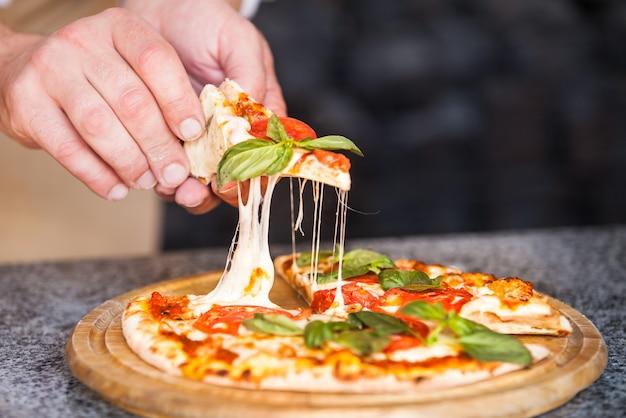 Cook preparing pizza in a restaurant.