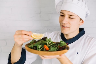 Cook putting lemon on plate with salad