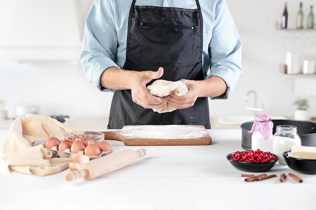 A cook on a rustic kitchen. the male hands with ingredients for cooking flour products or dough, bread, muffins, pie, cake, pizza