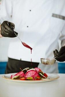 Руки повара в белой форме с черными медицинскими перчатками разливают заправку для салата. основное внимание уделяется ложке.