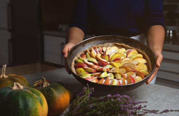 クックは、カラフルなリンゴを詰めたほぼ完成したパイを示しています