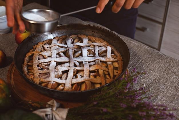 クックは、完成したケーキの表面に粉砂糖と茶漉しを振りかけます