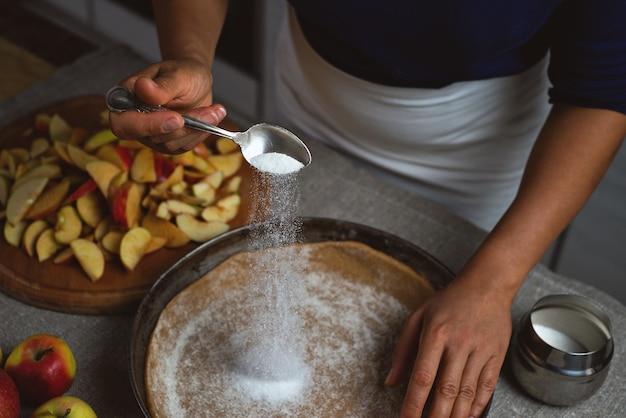 クックは、アップルパイ生地に銀スプーンから白砂糖を振りかけます。