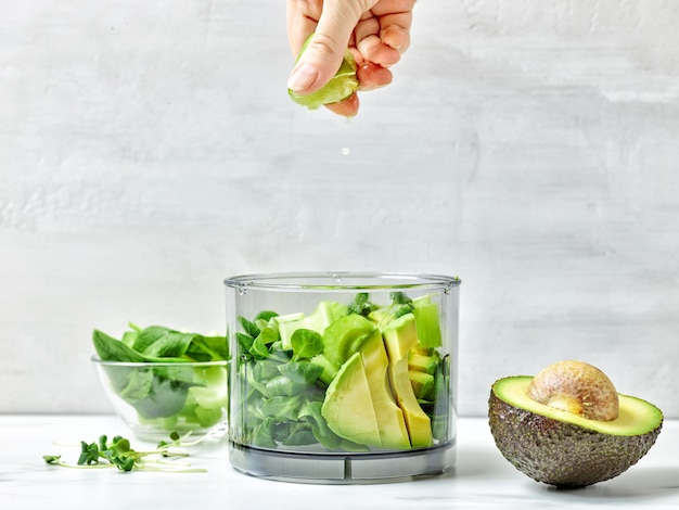 Cook squeezing lime into blender container for making healthy smoothie