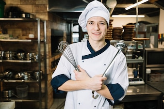 Cook standing with whisk and ladle in kitchen