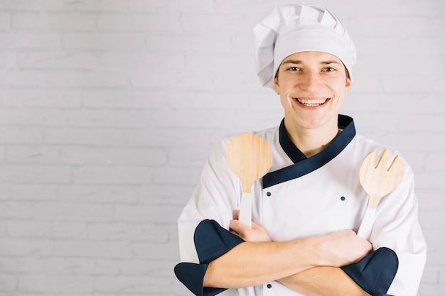 Cook standing with wooden kitchen utensils