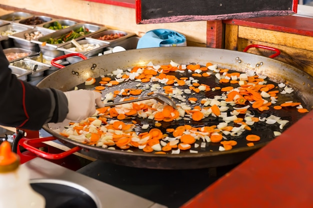 Cook stir frying fresh vegetables in a large pan on a buffet moving the diced veggies with a spatula