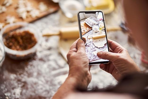 Повар фотографирует кухонное рабочее место на смартфоне
