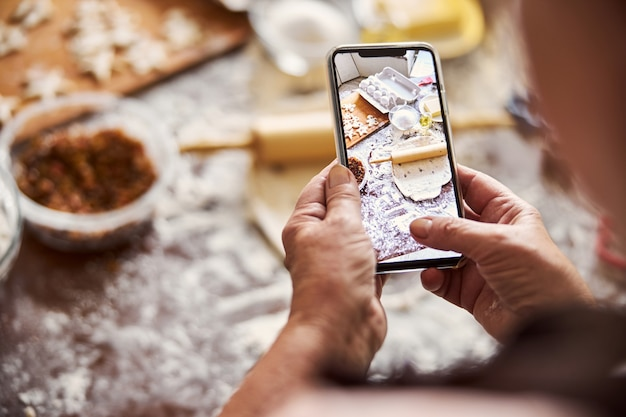 Cook taking a photo of kitchen workplace on smartphone