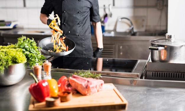Кук подбрасывает овощи на сковороде