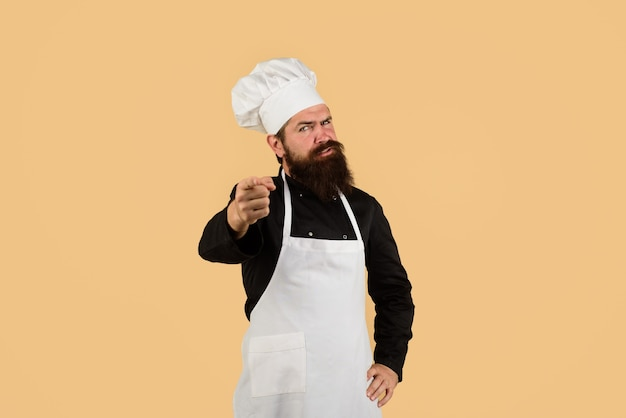 Cook in uniform pointing at you professional chef man in cook hat apron serious chef with beard