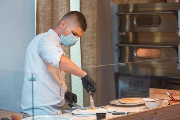 彼の仕事で医療用マスクを着用して料理する