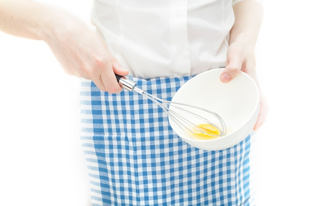 A cook whips an egg in a plate, dressed in a white shirt and blue apron