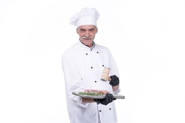 Повар с счастливым лицом, пожилой шеф-повар держит мясо стейка. человек с бородой, изолированные на белой стене