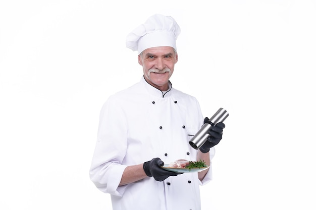 Cook with happy face, elderly chef male holds steak meat and pepper