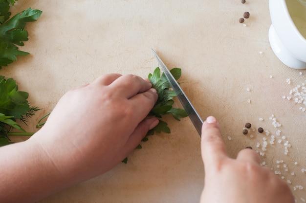나무 책상에 녹색 파 슬 리를 절단하는 여자 요리.