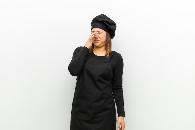 Cook woman feeling disgusted, holding nose to avoid smelling a foul and unpleasant stench