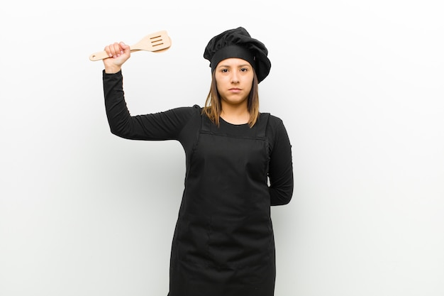 Cook woman feeling serious, strong and rebellious, raising fist up, protesting or fighting for revolution against white