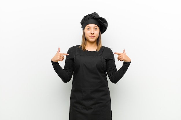Cook woman looking proud, positive and casual pointing to chest with both hands against white