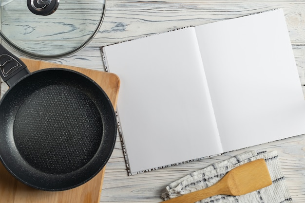 Cookbook and frying pan on wooden table