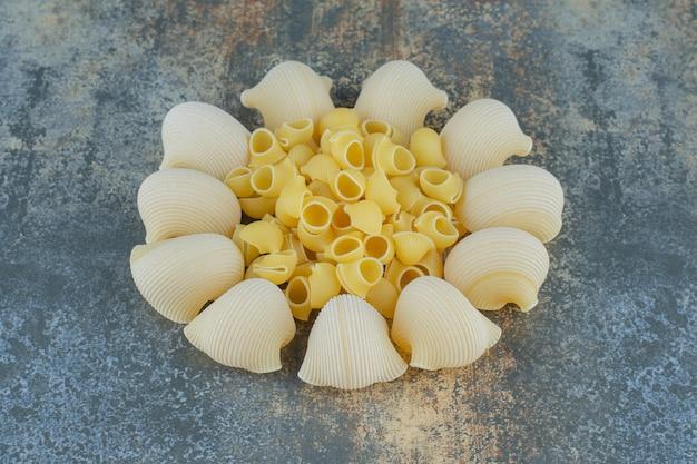 Приготовленные и сырые макароны в миске на мраморной поверхности.