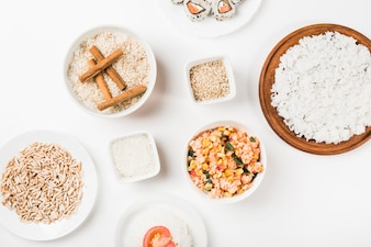 Cooked and uncooked rice on white background