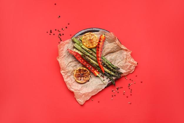 色の背景に唐辛子とレモンで調理したアスパラガス