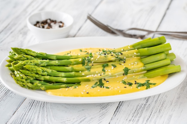 Cooked asparagus with hollandaise sauce on the serving plate