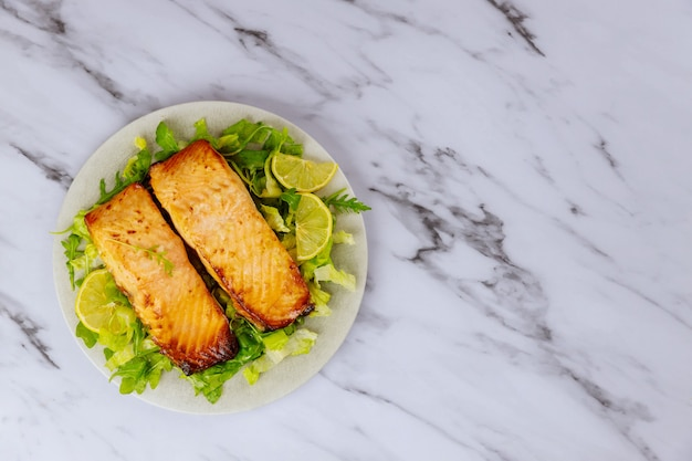 Cooked atlantic salmon in plate with salad and lemon on white