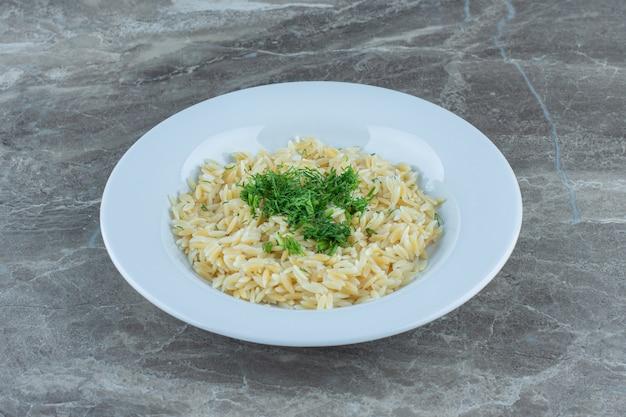 Приготовленный рис басмати в тарелке на мраморном столе.