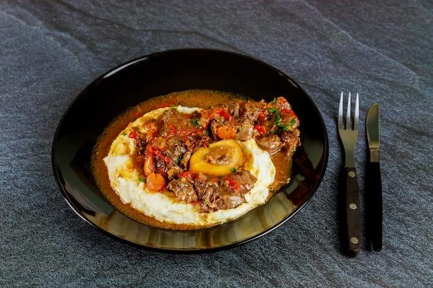 포크와 나이프로 검은 접시에 으깬 감자와 함께 요리된 쇠고기 정강이.