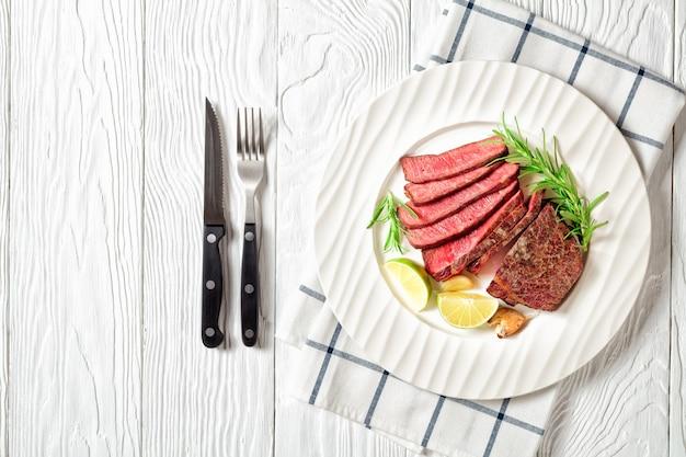 Приготовленный стейк из говяжьего филе, обжаренный и нарезанный, подается на белой тарелке с дольками розмарина и лайма на белом деревянном столе, со столовыми приборами для стейка, вид сверху, место для копирования