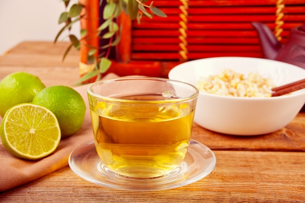 Cooked brown rice in white bowl with chopsticks and cup of green tea on the wooden background.