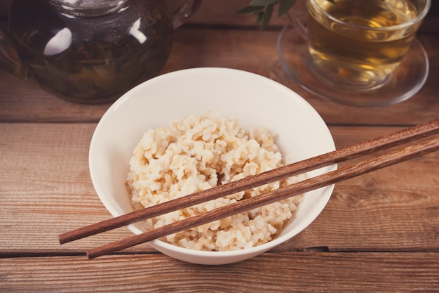 Cooked brown rice in white bowl with chopsticks on the wooden background.