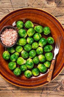 Приготовленная брюссельская капуста с зеленой капустой в деревенской тарелке с солью. деревянный фон. вид сверху.