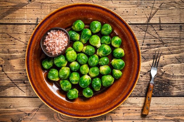 소금과 함께 소박한 접시에 요리 브뤼셀 녹색 콩나물 양배추