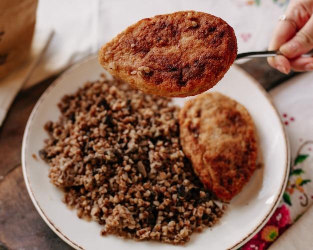 昼食時にカラフルなティッシュテーブルで白いプレートパンのローフの中の揚げ肉のスライスと共にそばを調理