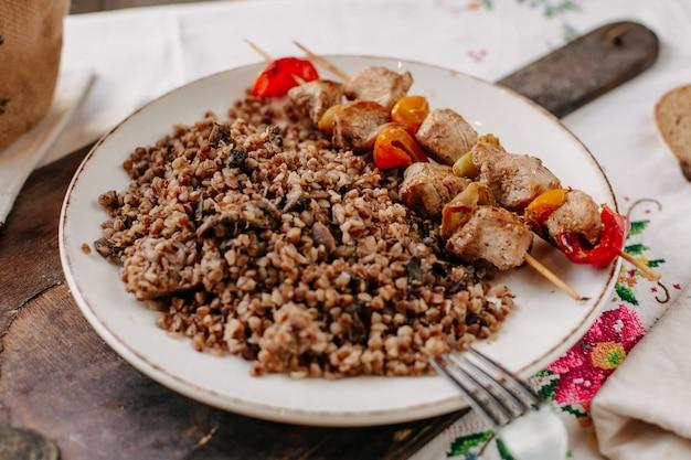 昼間のカラフルなティッシュテーブルの上の白いプレートのパンの塊の内側の小さな棒に揚げ肉のスライスと一緒に調理されたそば