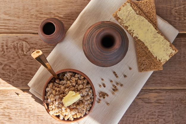 Cooked buckwheat cereal in brown clay bowl on wooden table. gluten free grain for healthy diet