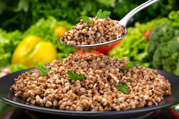 スプーンで調理したそば粥、黒いプレートにハーブと野菜を添えて