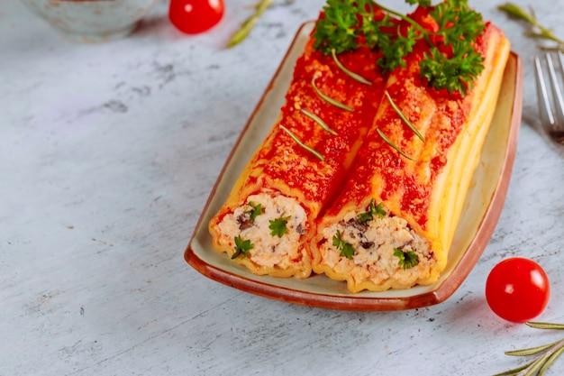 Приготовленные каннеллони на тарелке с томатным декором