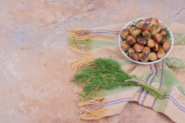 Khinkali caucasico cotto nel piatto bianco servito con erbe e spezie.
