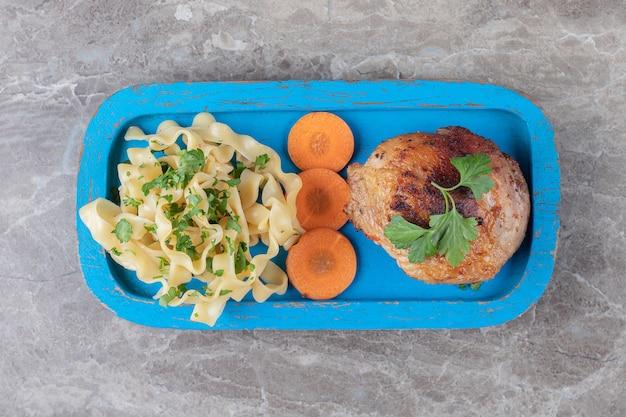 Приготовленная куриная голень, нарезанная морковь и макароны на деревянной тарелке, на мраморе.