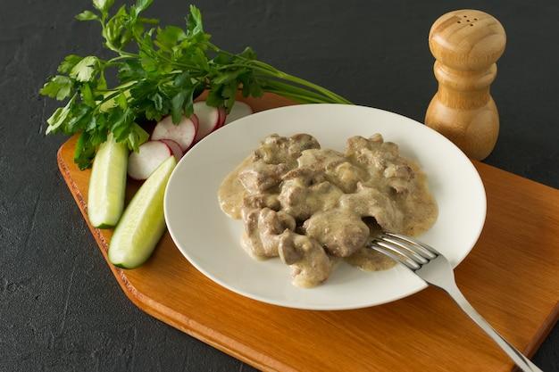 木製の机の上に盛り付けた皿に玉ねぎとサワークリームソースを添えて調理した鶏レバー。素朴なスタイル。
