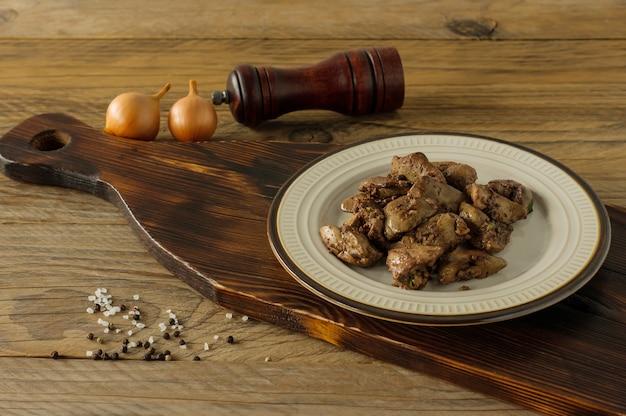 접시에 양파와 함께 요리된 닭 간은 나무 책상에 제공됩니다. 소박한 스타일.