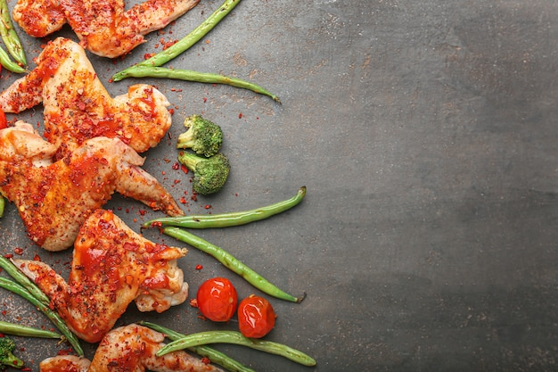 어두운 테이블에 야채와 닭 날개 요리